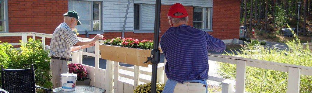 Kuvassa asiakkaat kunnostavat Tammikodin terassin kaidetta.